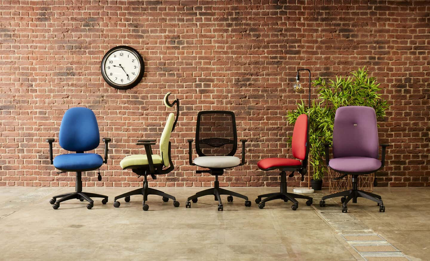 A group of 5 ergonomic office chairs in front of an exposed brick wall with a clock and a plant behind