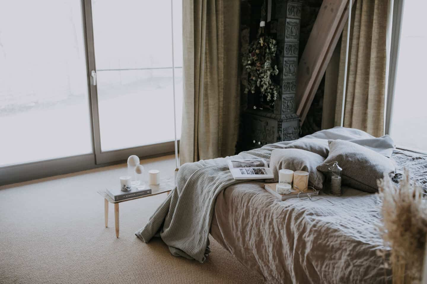Textured Lives. Using texture in interiors to bring your home to life.  A bedroom with floor to ceiling wondows and natural light pouring in. The bed has a linen cover and there are books, candles and cushions on the bed.