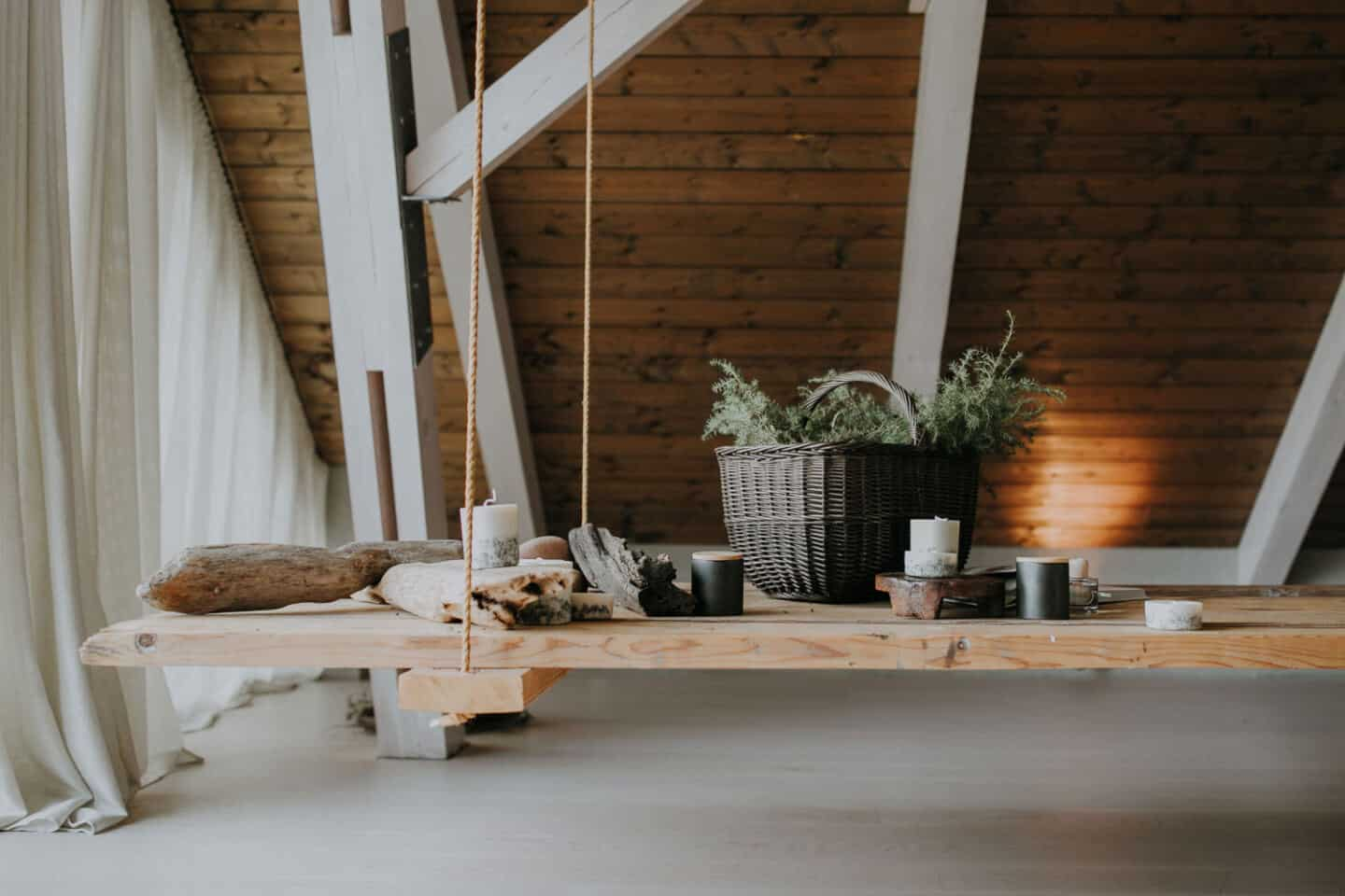 Textured Lives. Using texture in interiors to bring your home to life.  Candles and a basket of moss displayed on a wooden swing in a loft room.