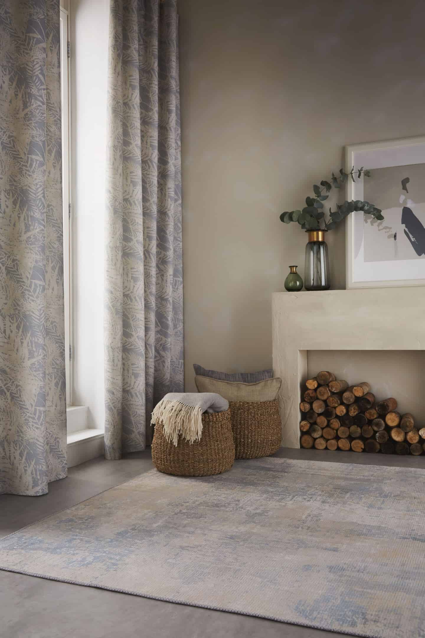 Textured Lives. Using texture in interiors to bring your home to life.  Curtains with a nature-inspired pattern on them hang in a doorway. Two baskets next to a fireplace full of throws blankets and cushions.