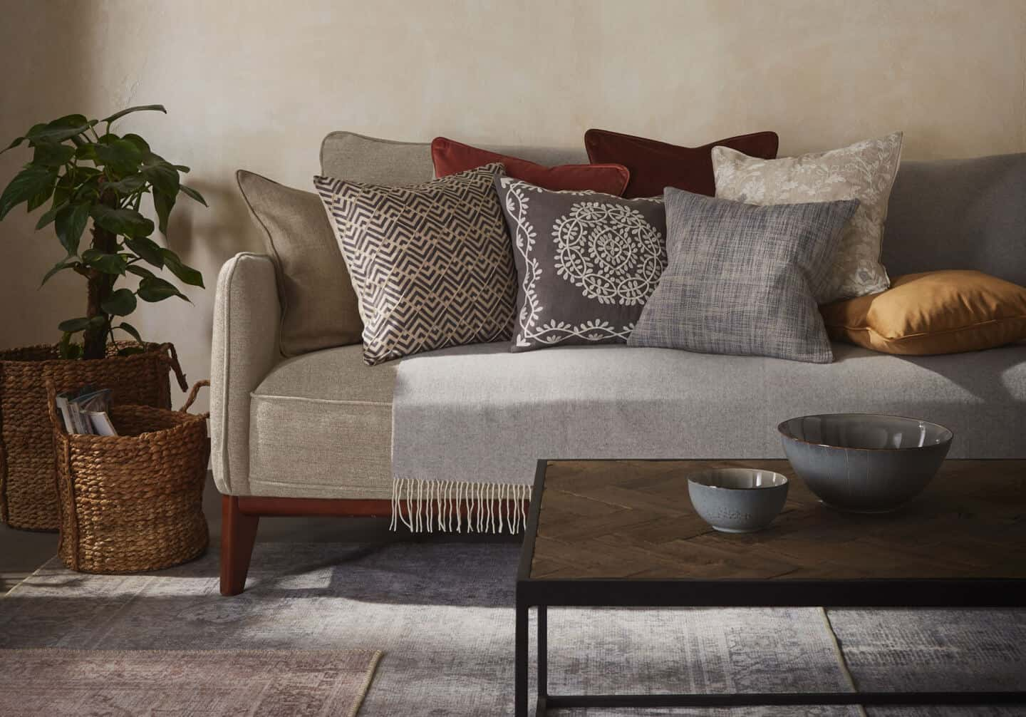 Textured Lives. Using texture in interiors to bring your home to life.  A sofa is behind a coffee table whoch is on a rug. The sofa is covered in textured cushions in an earthy colour palette