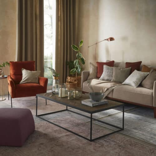 a living room featuring sofa, armchair and coffee table with lots of textured accessories