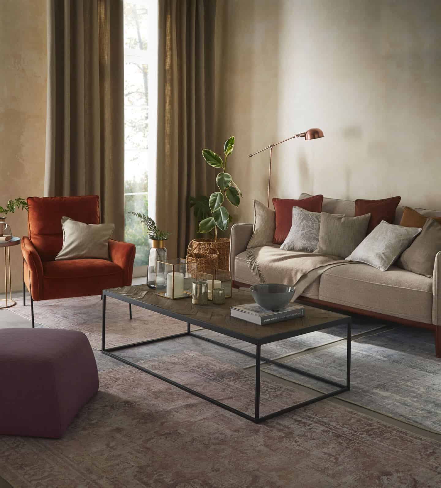 Textured Lives. Using texture in interiors to bring your home to life. A living room featuring sofa and armchair and pouffe around a coffetable on a rug.  A window with curtains is behind the armchair.