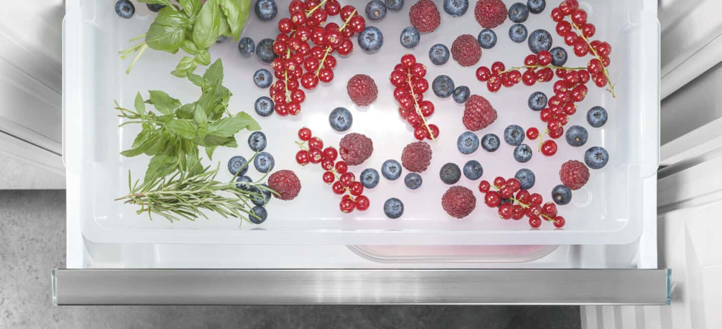 Liebherr's fully integrated appliance range. A freezer drawer full of berries and herbs.