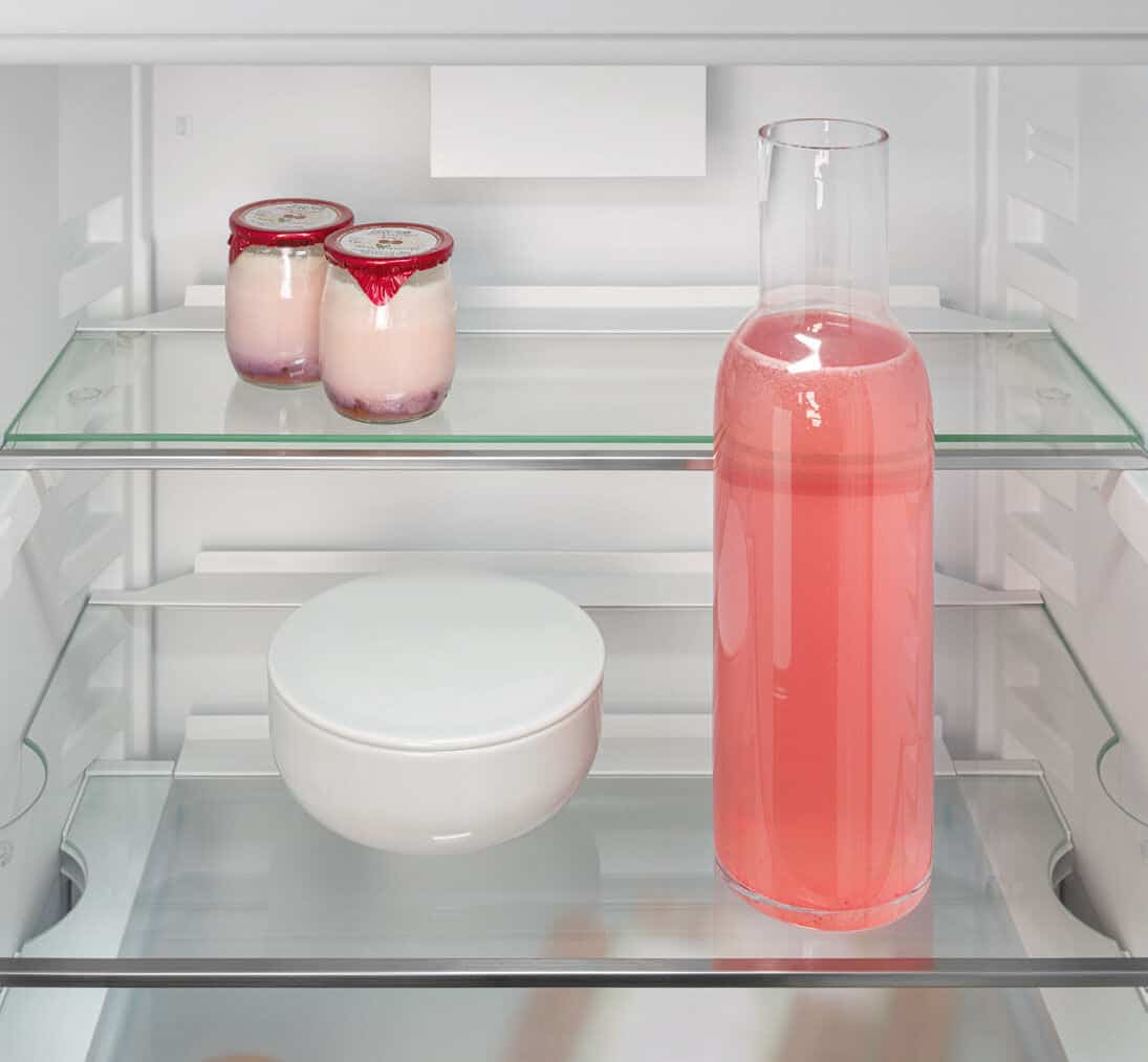 Liebherr's fully integrated appliance range. A glass shelf is divided in two to make space in the fridge for a tall bottle.