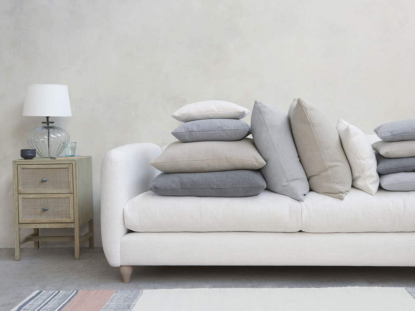 A squishy white sofa in bamboo fabric is covered in cushions. Bamboo is a great material for sustainable interior design