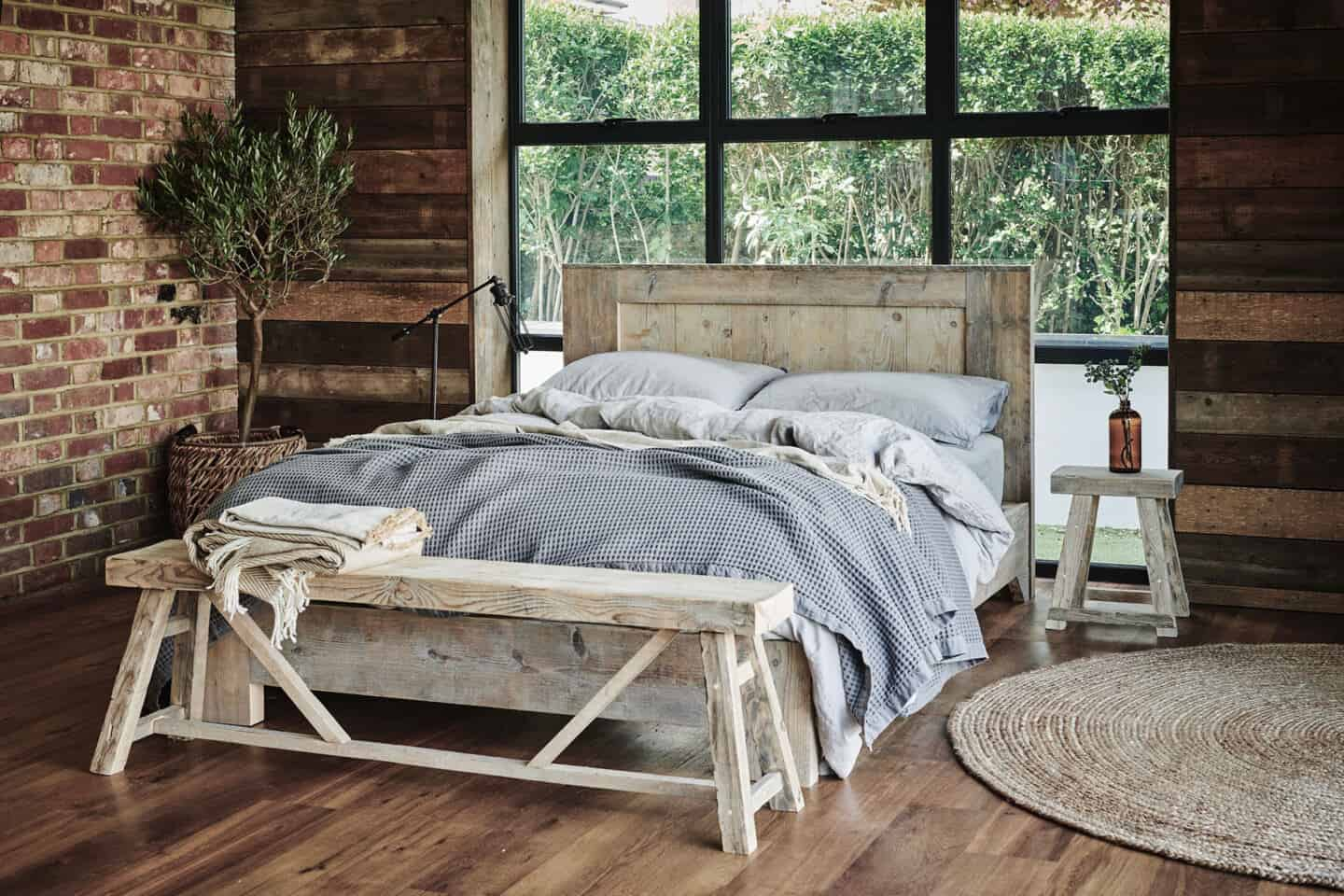 A double bed and two benches made from reclaimed wood which is a great material for sustainable interior design