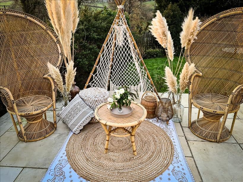 Entertain outdoors with two peacock chairs set up surrounded by large vases full of pampas grass, lanterns, pouffes and a macrame tipi