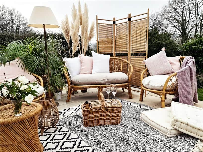 Entertain outdoors by setting up an outdoor living room. Use rattan furniture, rugs, cushions, blankets, a coffee table, side table, a lamp, and a wooden screen.