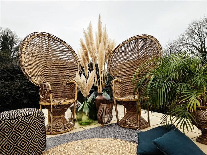 Entertain outdoors with two peacock chairs set up on rugs surrounded by large vases full of pampas grass