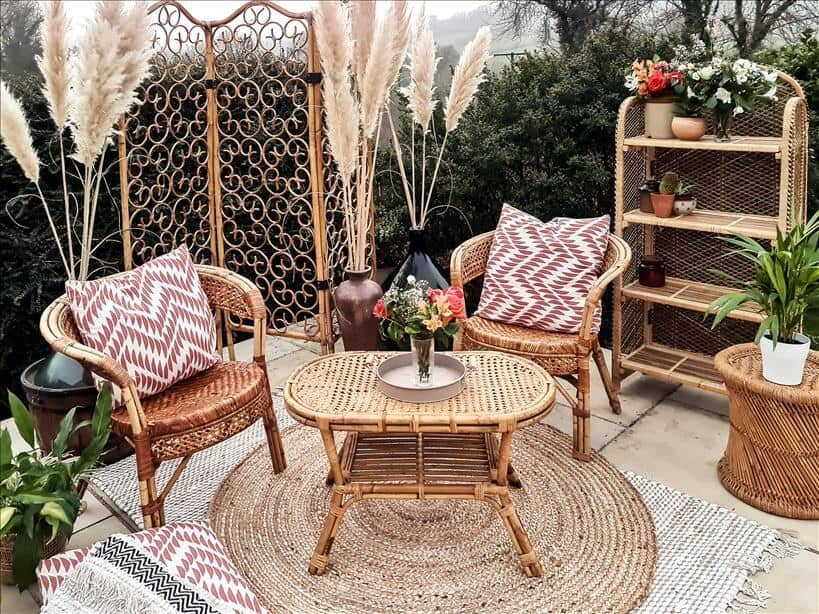 Entertain outdoors by setting up an outdoor living room. Use rattan furniture, rugs, cushions, a coffee table, a shelving unit and a wooden screen.
