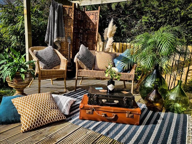 Entertain outdoors by setting up rattan furniture , rugs, cushions, large vases, a wooden screen and vintage suitcases
