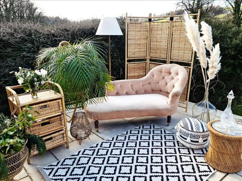 Entertain outdoors by setting up a chaise longue, rugs, pouffes, lamps, vases, lanterns and a wooden screen