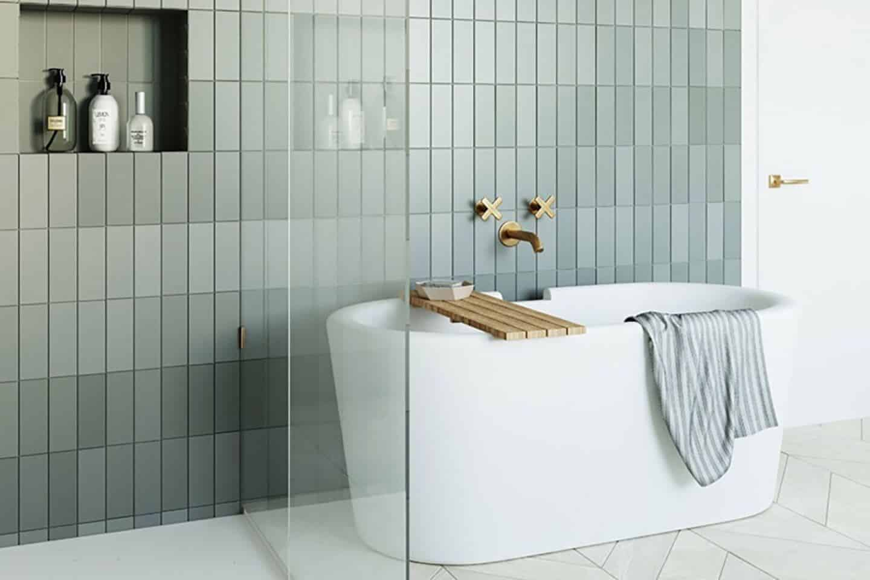 Arielbath freestanding bathtub with grey tiled wall behind.