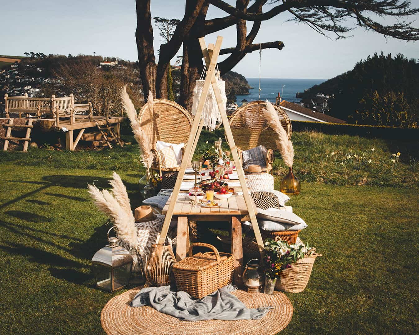 Beautiful boho picnic set up in a garden overlooking the mouth of the river dart