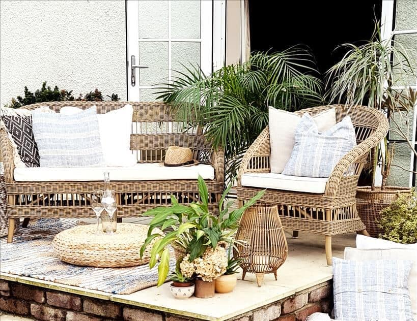 Entertain outdoors by setting up rattan furniture, rugs, cushions, pouffes and lanterns