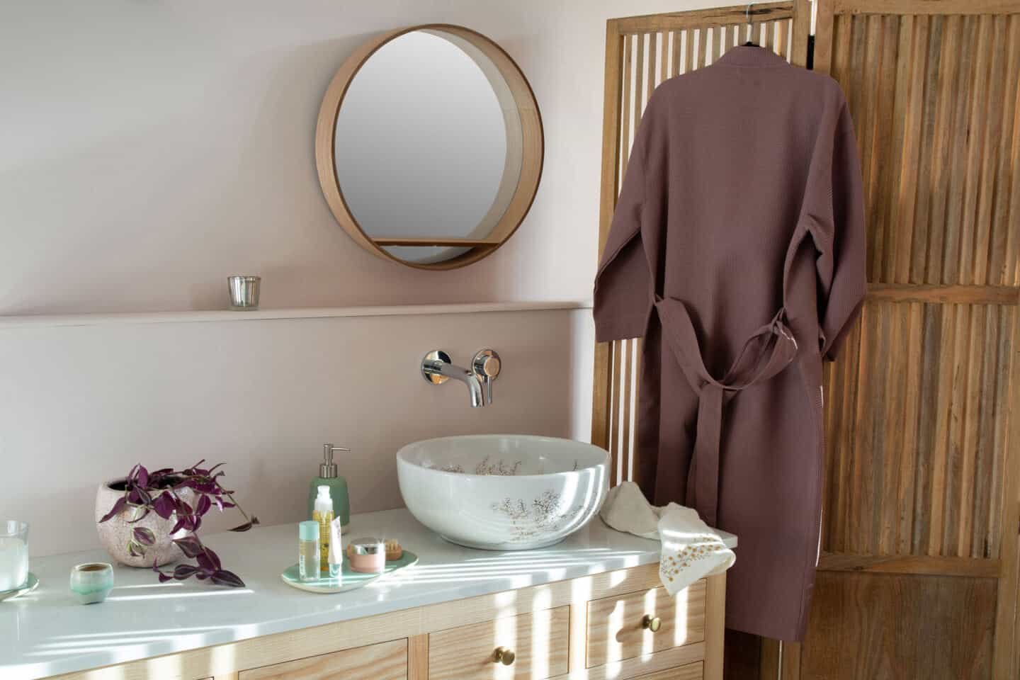A round white bathroom sink with vanity. The sink is covered in delicate blossom pattern and rests on a countertop in a Japanandi style bathroom