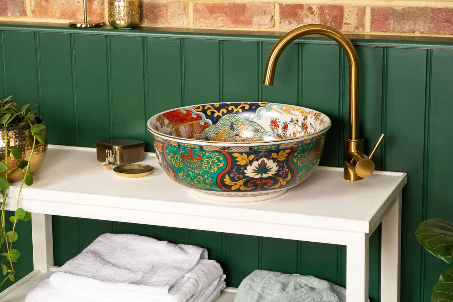 An round bathroom basin with oriental style pattern and colours rests on a vanity unity in front of a green wall