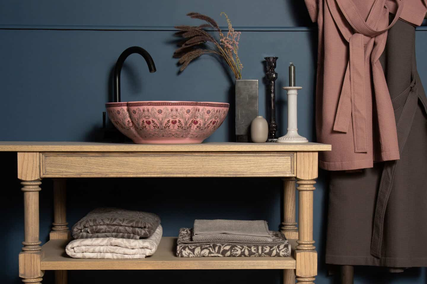 A scalloped pink bathroom basin with delicate floral patterning rests on a wooden vanity unit with a blue wall behind