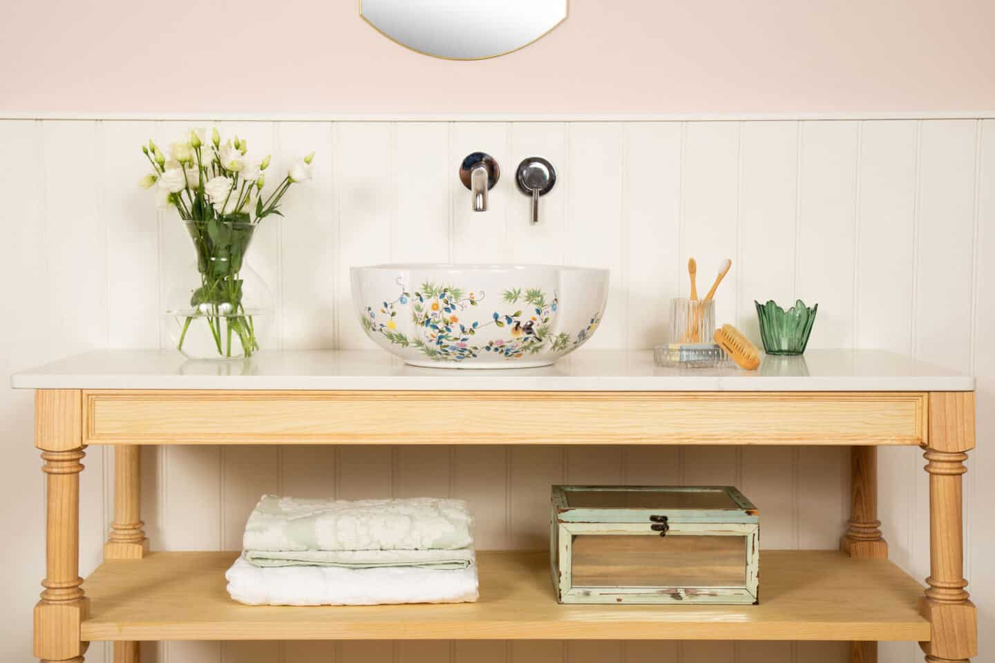 A round white bathroom basin with floral patterning rests on a wooden vanity unit