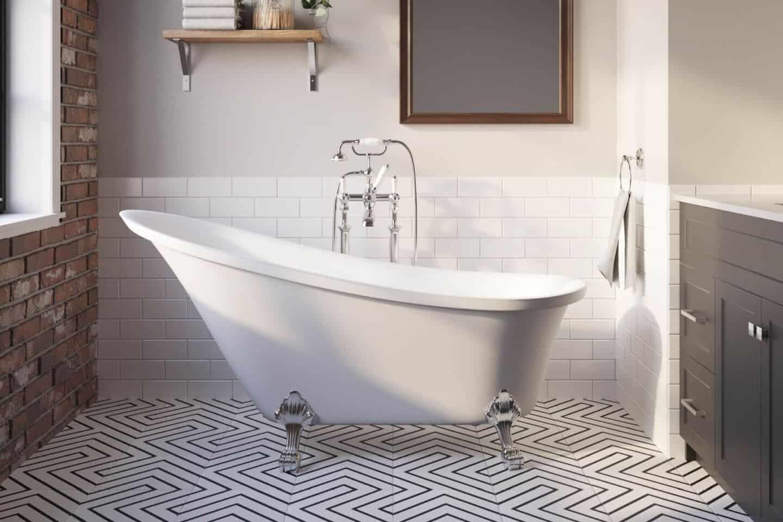 Arielbath freestanding slipper bath on patterned tile floor with dark vanity unit to the side