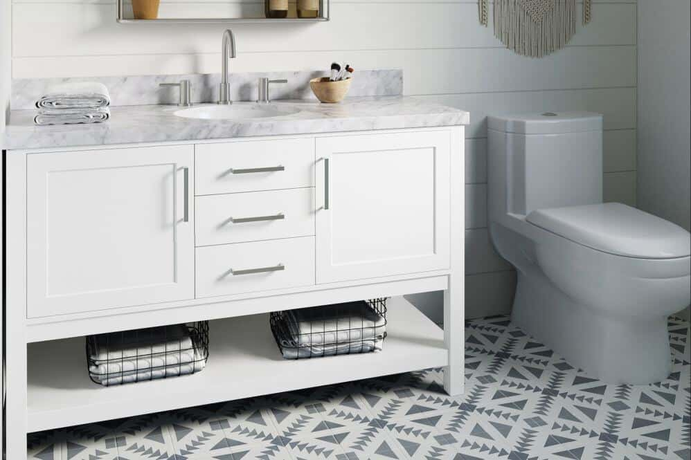 Arielbath white vanity with marble effect counter beside toilet. Black and white patterned tile floor