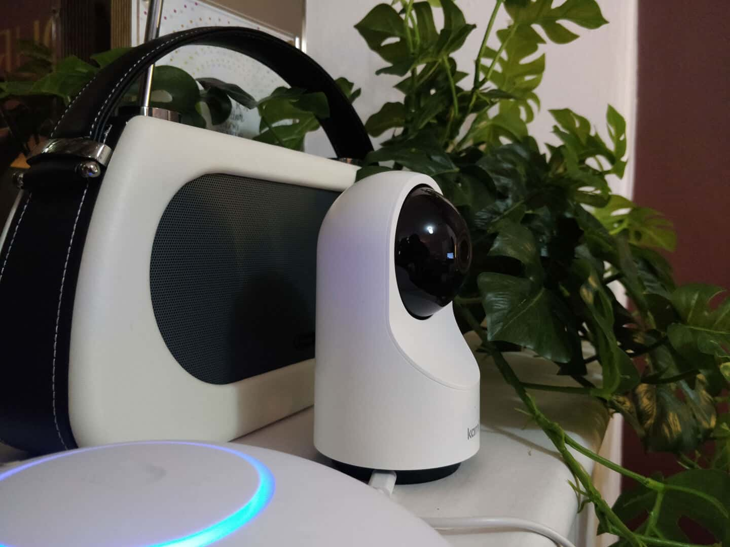 Kami indoor home security camera on a shelf with a radio, a faux plant and an internet hub