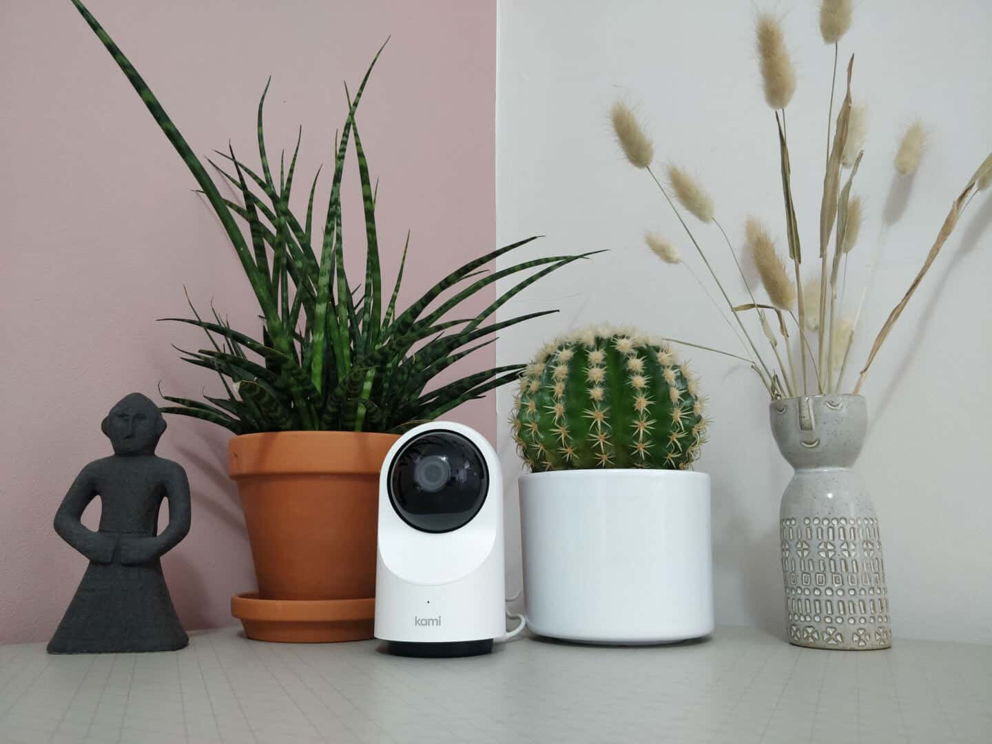 Kami indoor home security camera on a table between two plants and vase and a statue.
