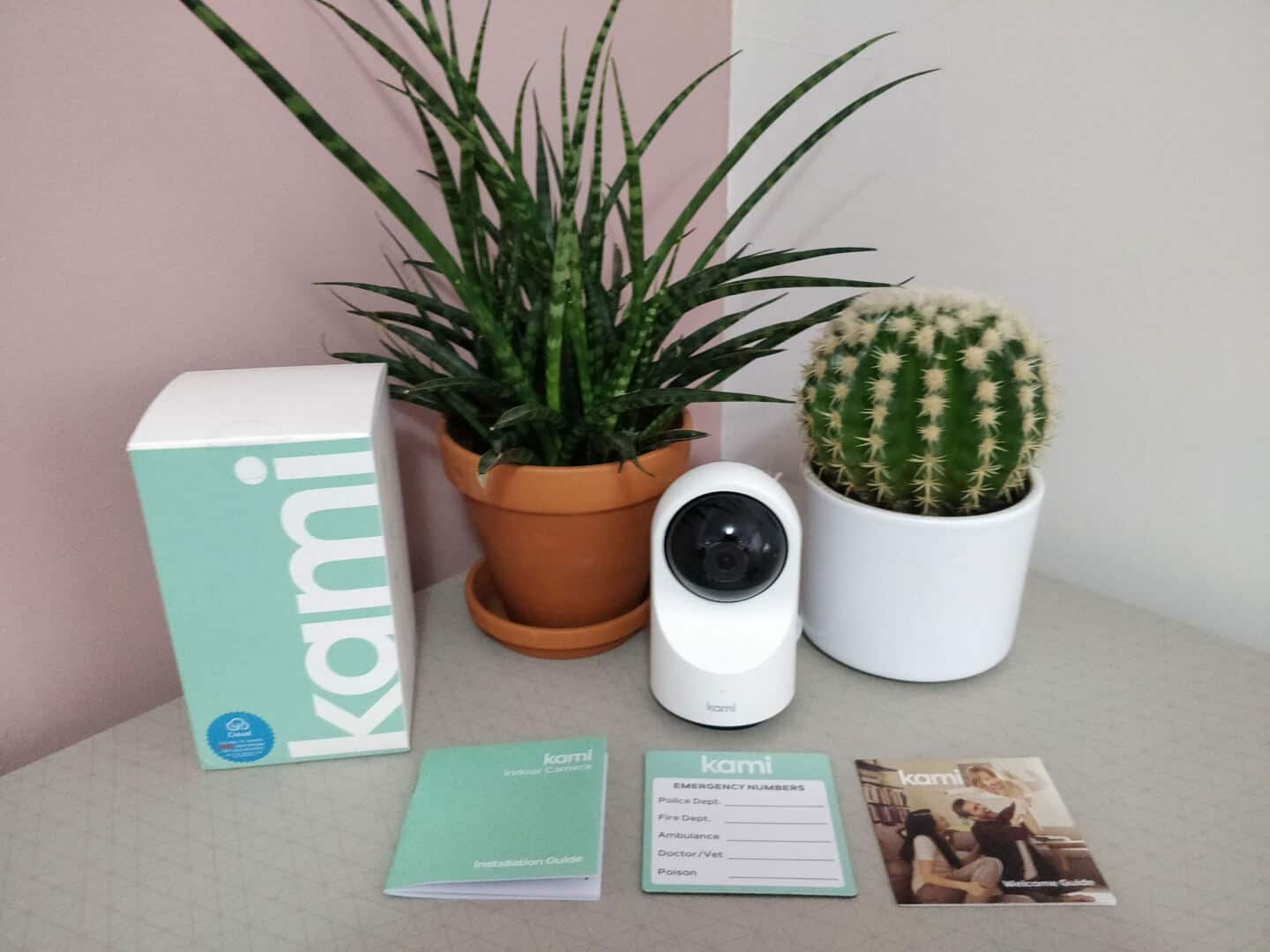 Kami indoor home security camera on a table between two plants. The empty box and leaflets are also on the table