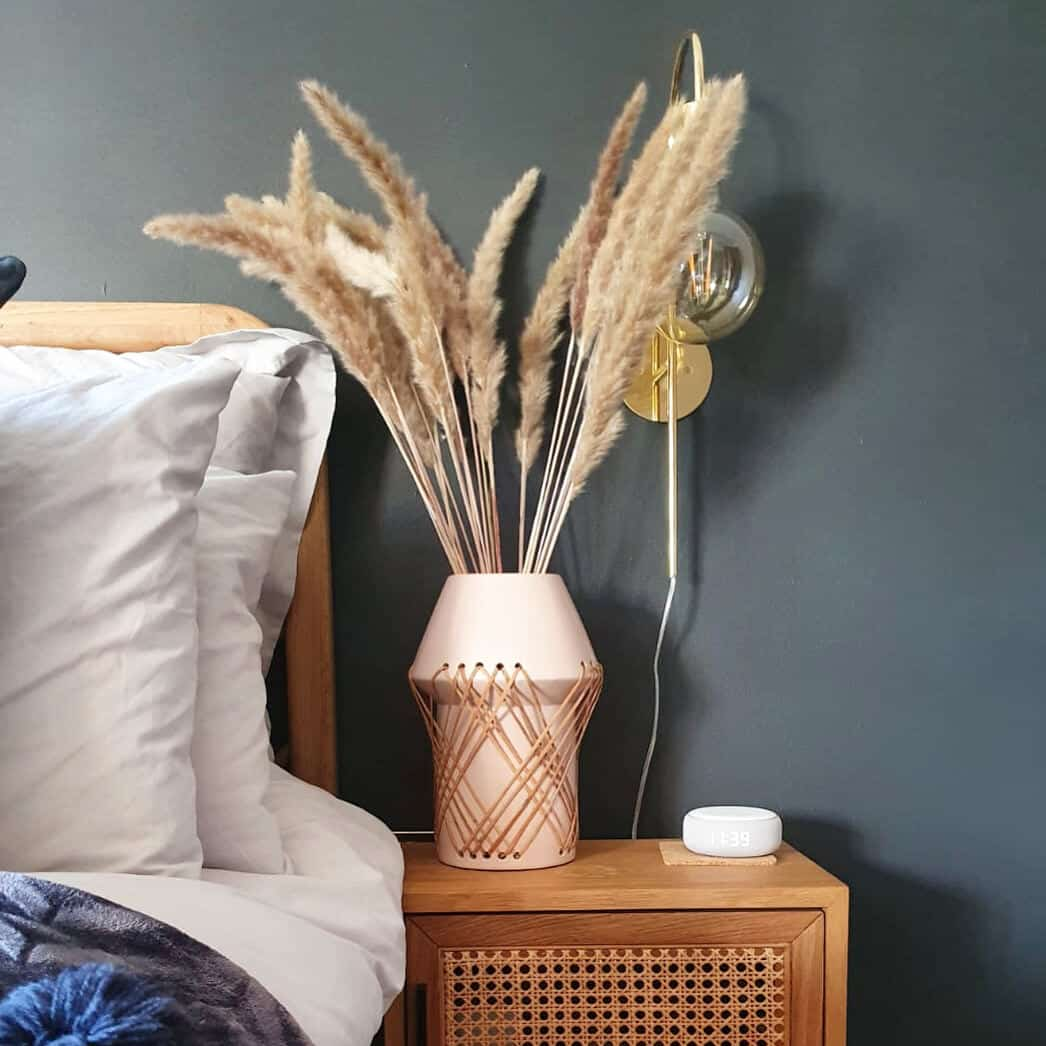 Affordable luxury homewares from Price & Coco Interiors. Vase of pampas grass on a rattan bedside table against a blue wall.