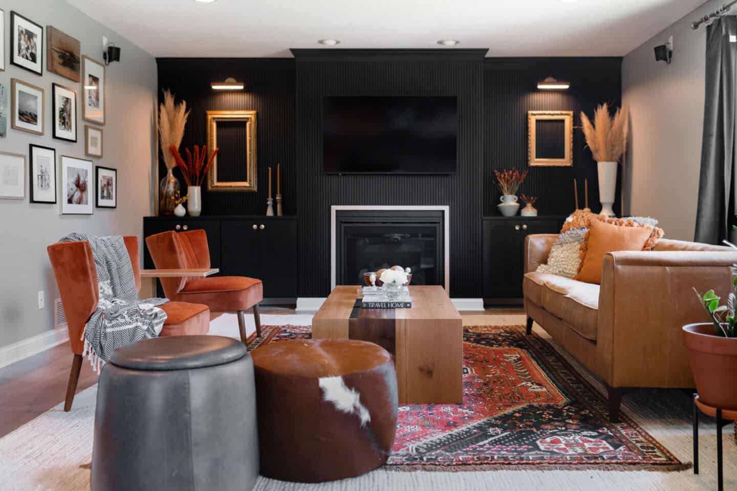 A living room with a black vertical wooden slat  panelling wall by Construction2style