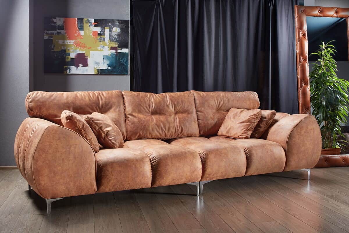 How to choose the perfect sofa for your lifestyle. Brown suede sofa on wooden floor with artwork behind and mirror to the right.