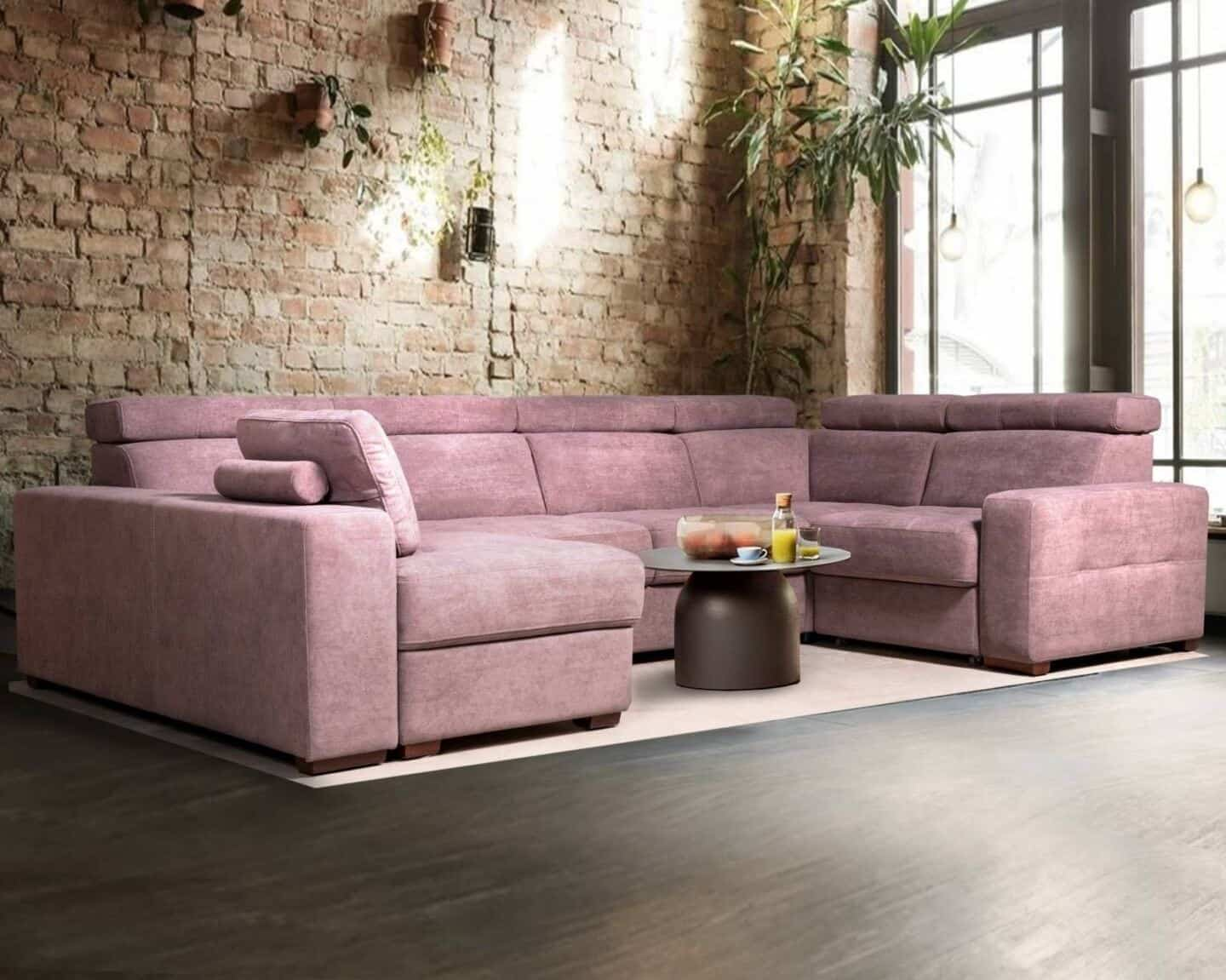 How to choose the perfect sofa for your lifestyle.  Modular pink sofa in anfront of an exposed brick wall with plants hung on the wall and a large window to the right.
