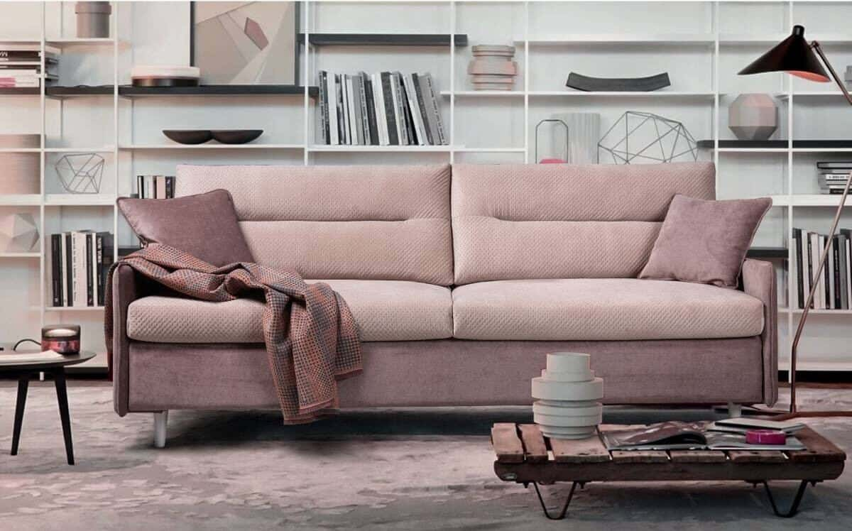 How to choose the perfect sofa for your lifestyle. Pink sofa bed in front of floor to ceiling shelving