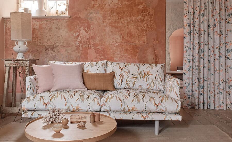 Made-to-Measure Curtains & Blinds using Romo fabric. A sofa in botanical print sits in front of a distressed terracotta wall with long curtains to the right and a round wooden coffee table in front.