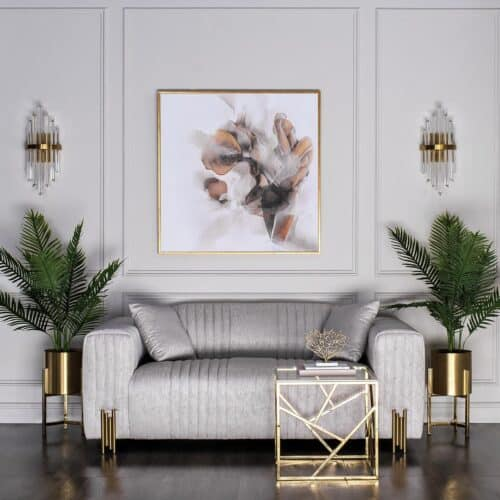 Grey sofa with brass legs against a grey panelled wall