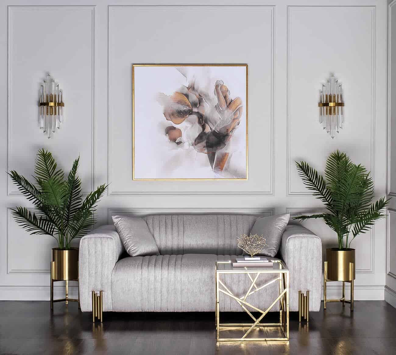 Small grey sofa with brass legs in front of grey panelled wall with plants either side in brass pots