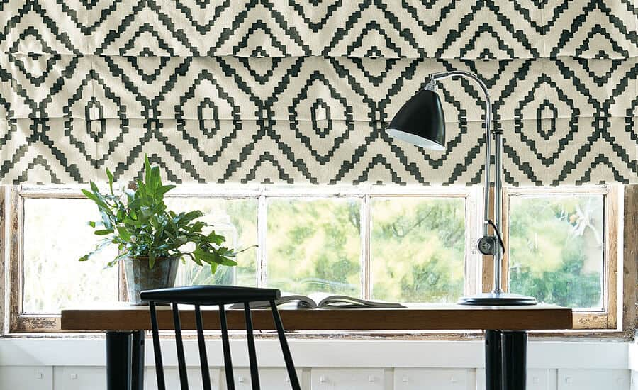 Made-to-measure blinds in Norrland fabric by Villa Nova. A desk sits in front of the window