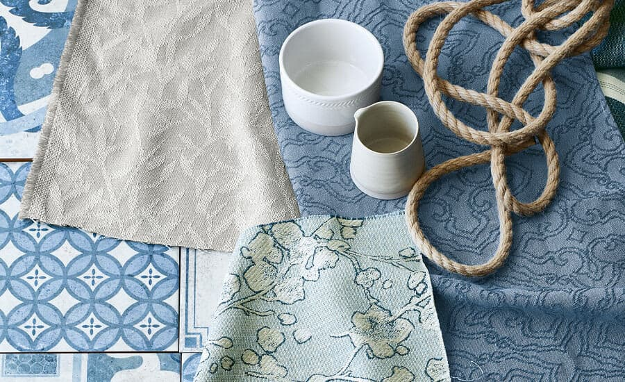 Aylin fabric by Villa Nova in shades of blue laid out on top of some blue tiles