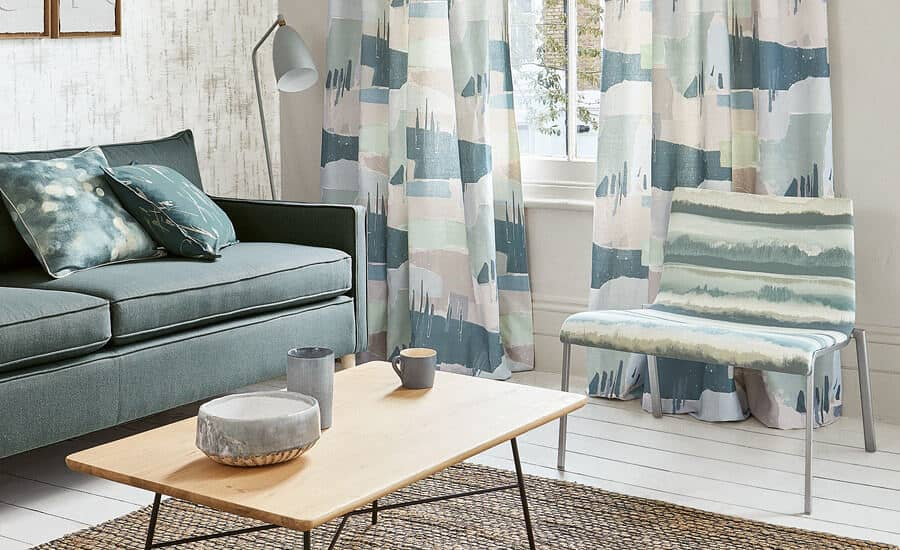 Made-to-Measure Curtains in Villa Nova fabric hang in front of a window. A sofa, chair and wooden coffee table sit in front of the window.