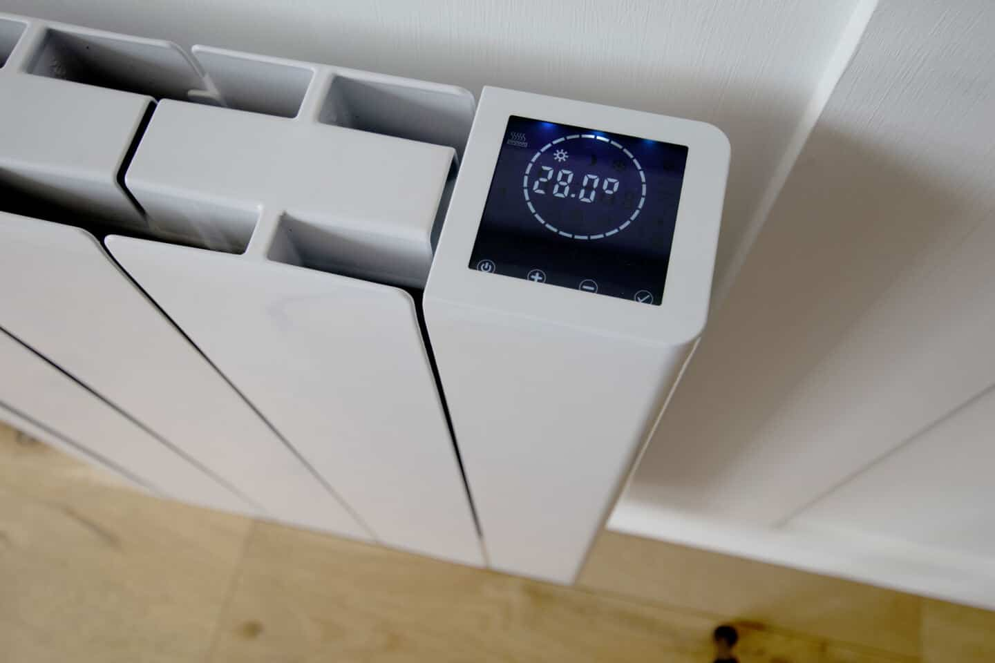 The digital display of the Ecostrad iQ Ceramic smart electric radiator mounted on a white wall.