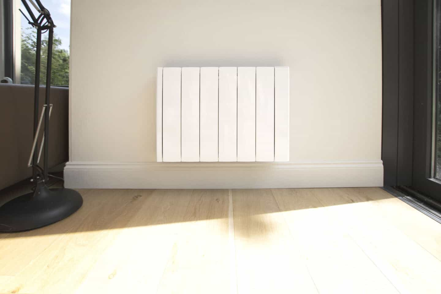 The Ecostrad iQ Ceramic smart electric radiator mounted on a white wall