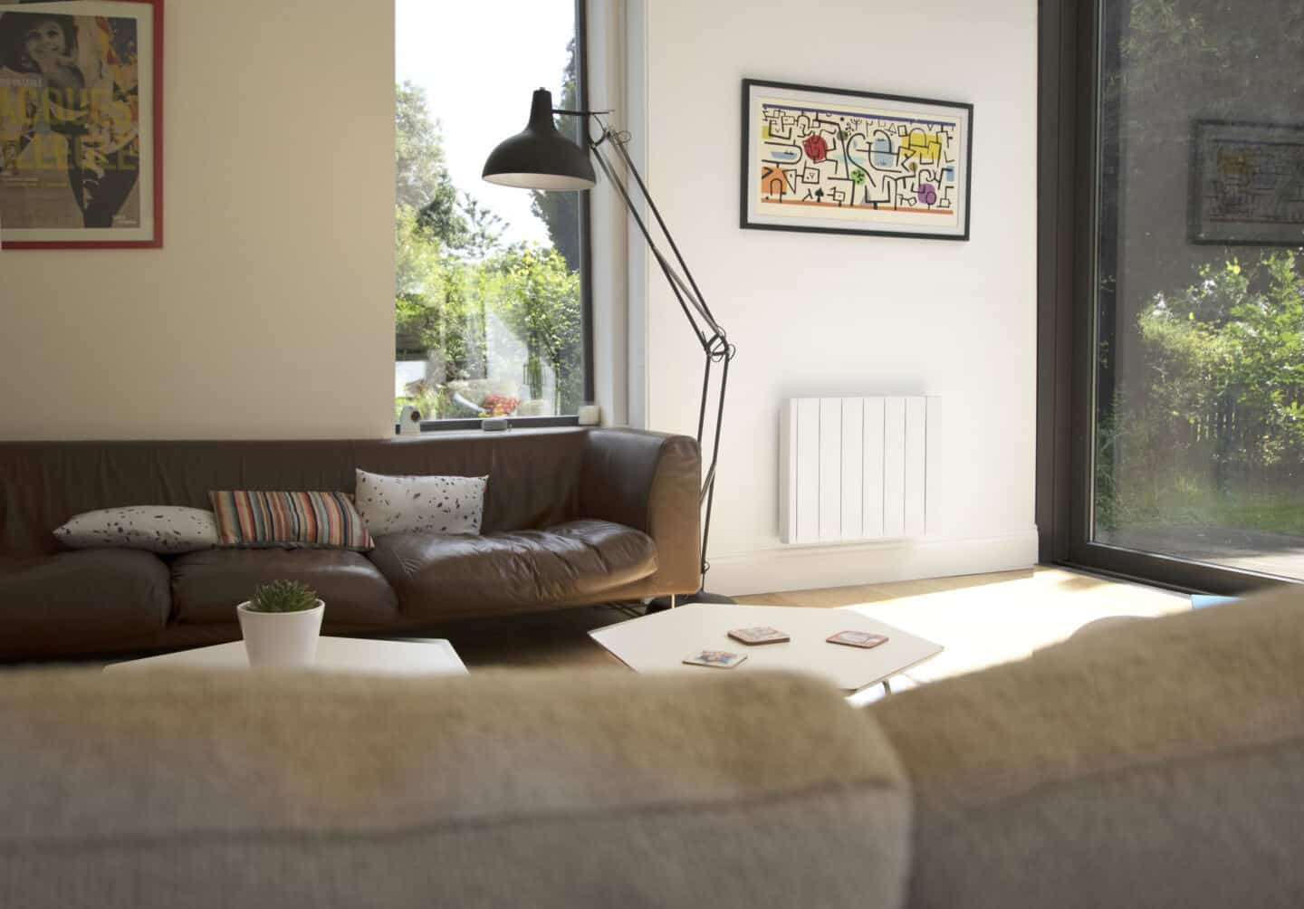 The Ecostrad iQ Ceramic smart electric radiator on a white wall in a modern living room