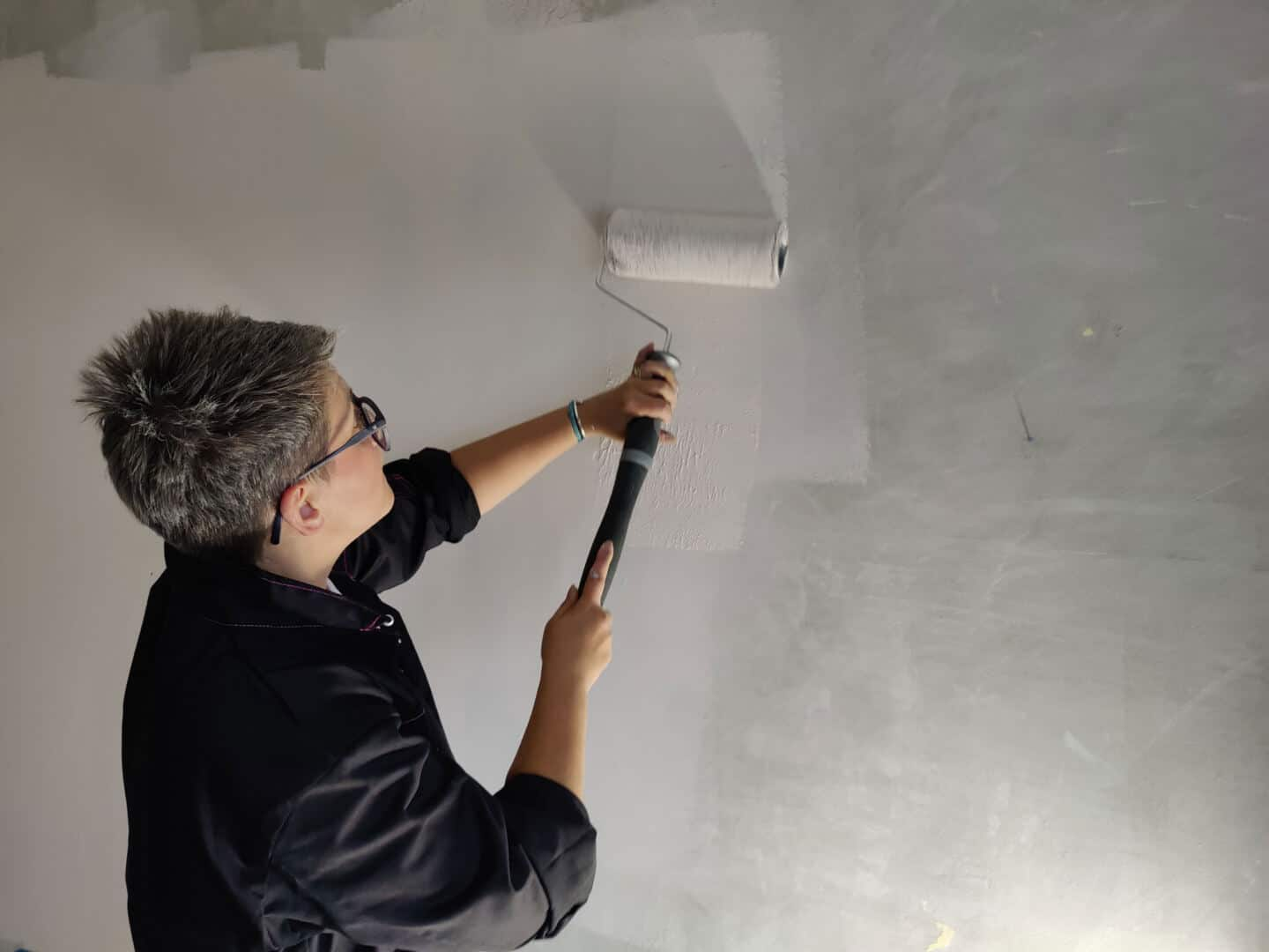 Blogger Stacey Sheppard applying Dulux Simply Refresh Paint to a wall with a roller in preparation for creating a DIY Painted Arch Accent Wall