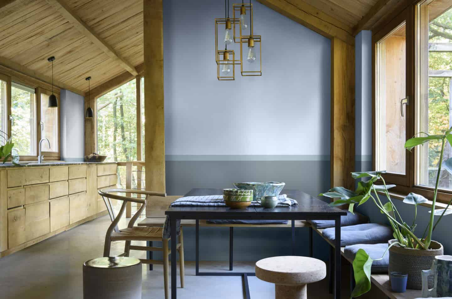 A rustic wooden kitchen and dining area with walls panted in Dulux Colour of the Year 2022 Bright Skies