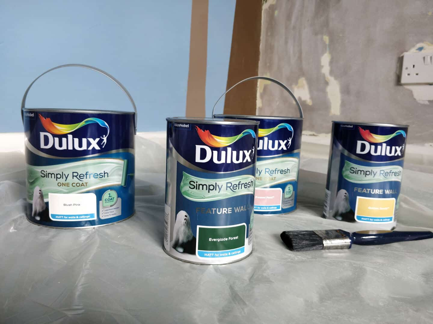 Dulux Simply Refresh paint cans on a plastic cover with a paintbrush. These colours will be used to create a DIY Painted Arch Accent Wall