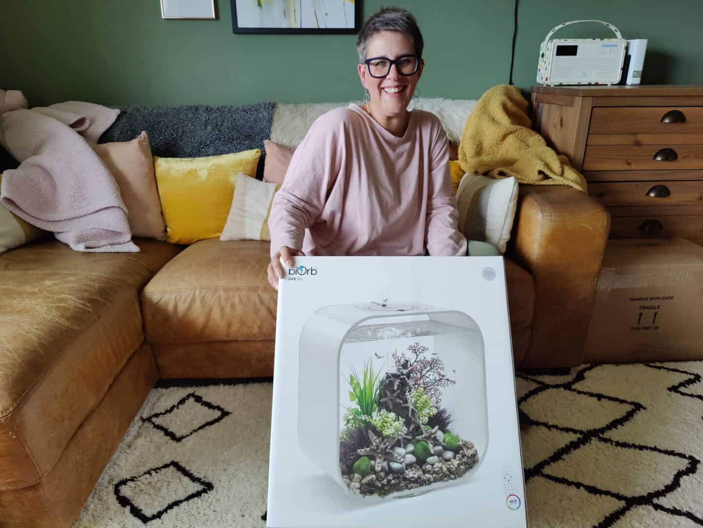 Interior design blogger Stacey Sheppard sat on a tan leather sofa holding a biOrb fishtank box