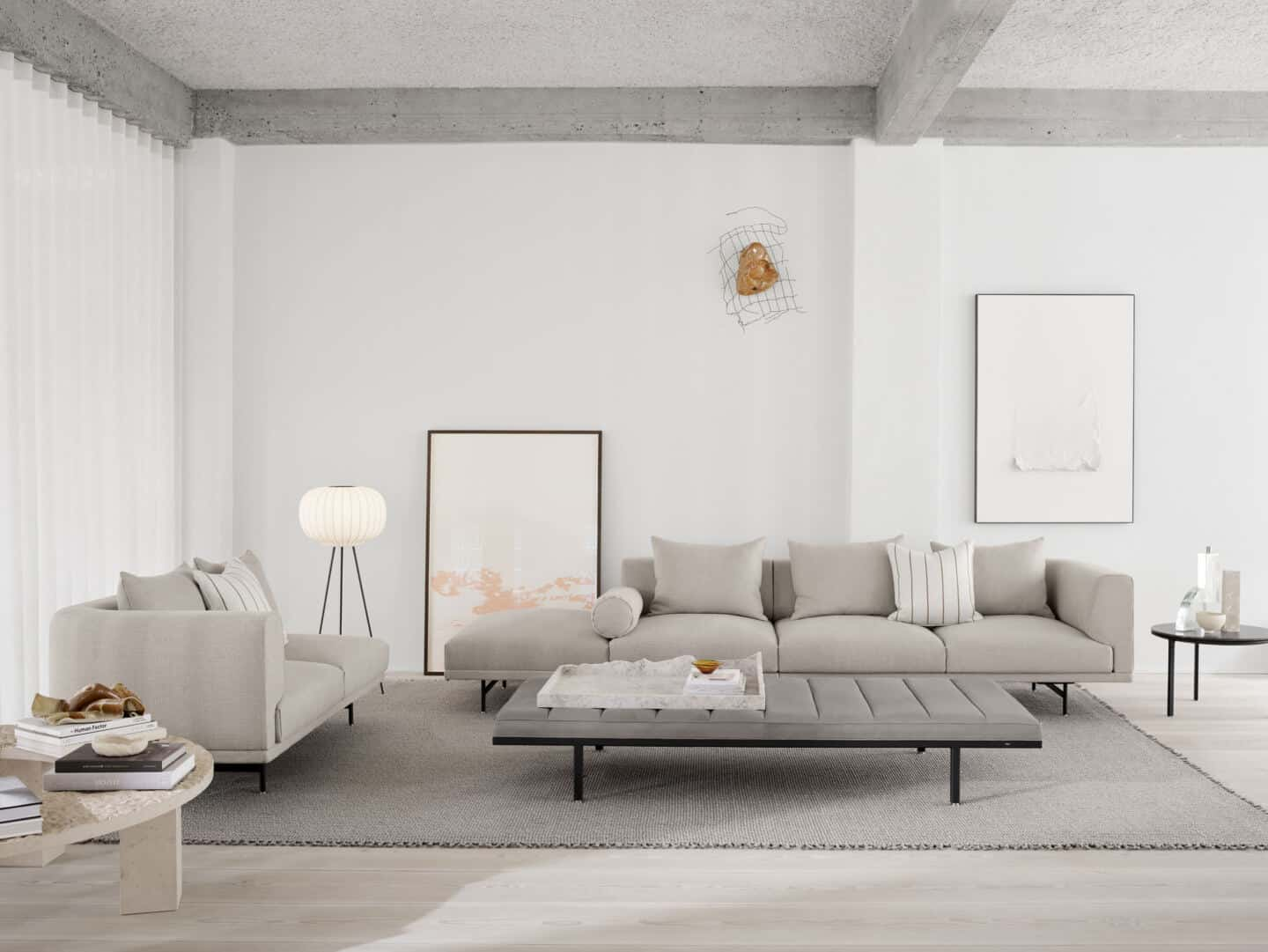 Japandi living room featuring low grey sofas and a low grey coffee table with a floor-standing paper light from Vipp